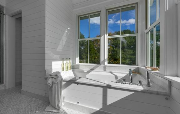 Stunning all-white bathroom with double-hung windows