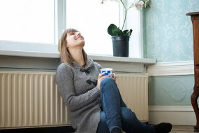 A homeowner relaxes next to a radiator in her home.