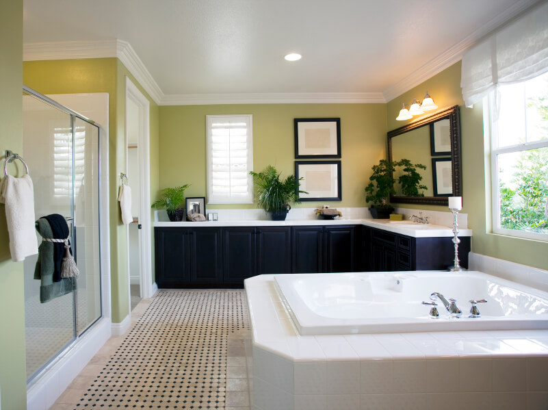 Green bathroom with shower, dark cabinets, tile floor, and jetted bathtub.