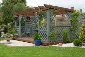 A pergola and deck in an English urban garden.