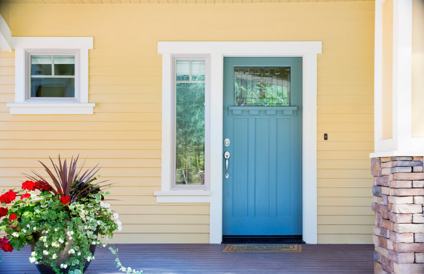 A blue front door on a yellow house.