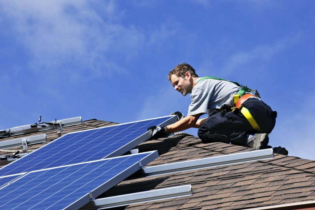 A contractor installs solar panels on a roof.