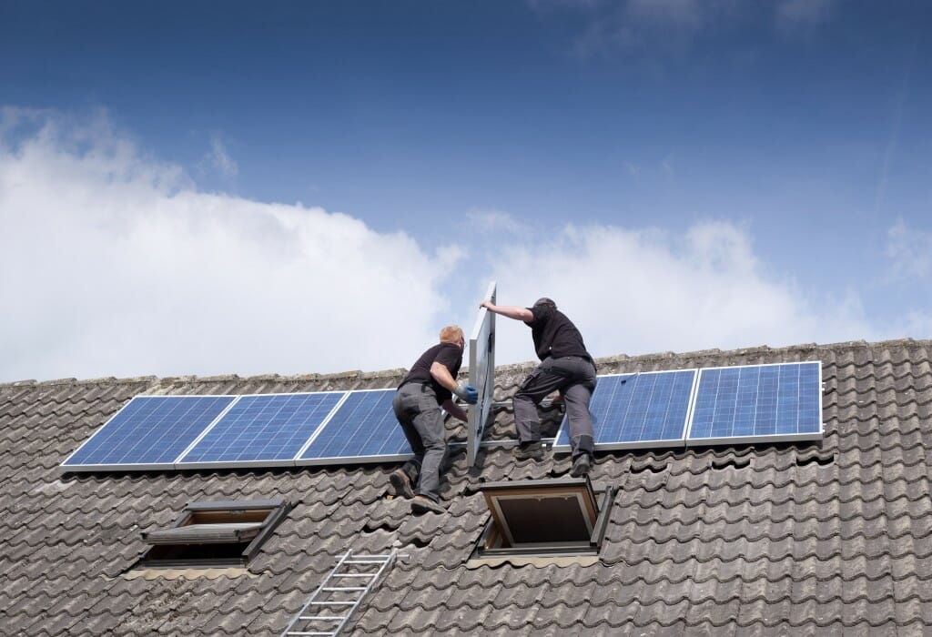 Two contractors work on installing solar panels on a roof.
