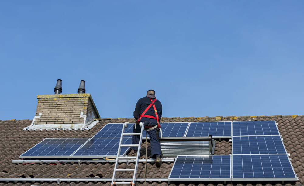 A contractor installs solar panels on a roof