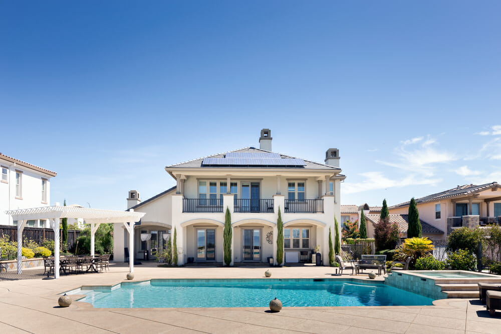 A large home with a pool in front of it.