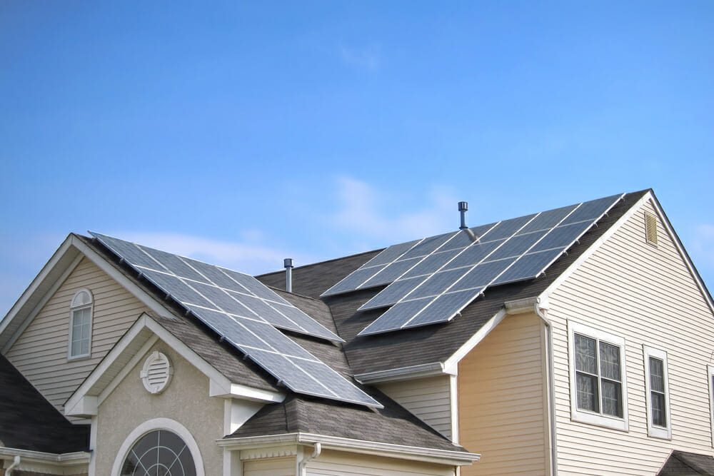 Solar panels on top of the roof of a house.