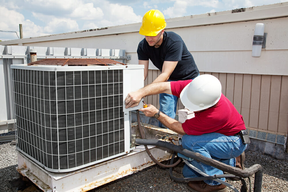 Two contractors work together on repairing an hvac unit.