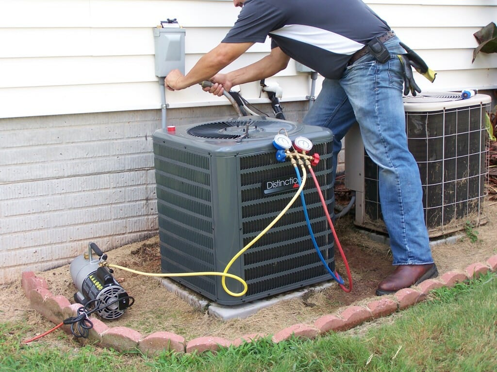 Contractor working outside on an hvac unit with central air conditioner prices cost calculator.