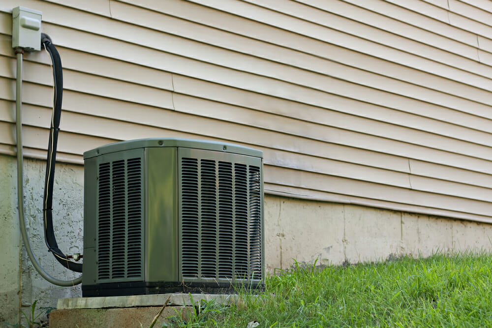 An air conditioner connected to the outside of a home. How do air conditioners work