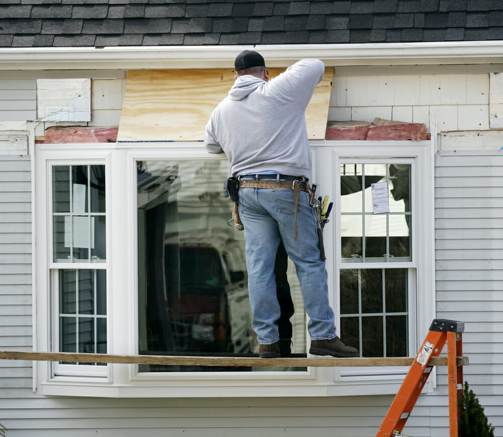 A contractor installs a bay window into a home