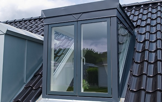 Casement window protrudes from the roof of a home.
