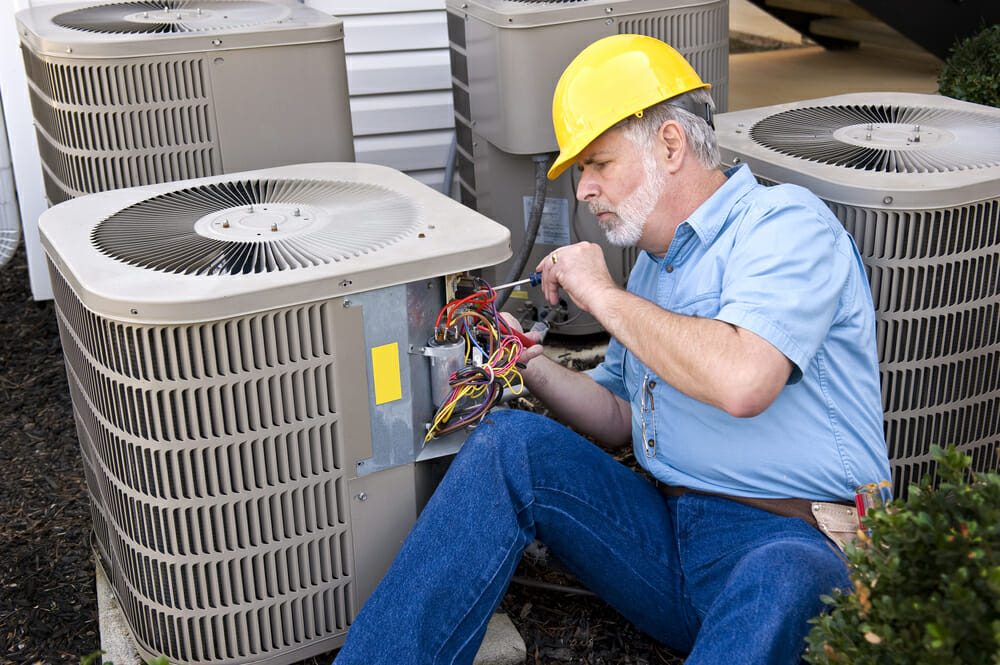 central air conditioner repair installation modernize a contractor works on repairing an hvac unit new ac installations