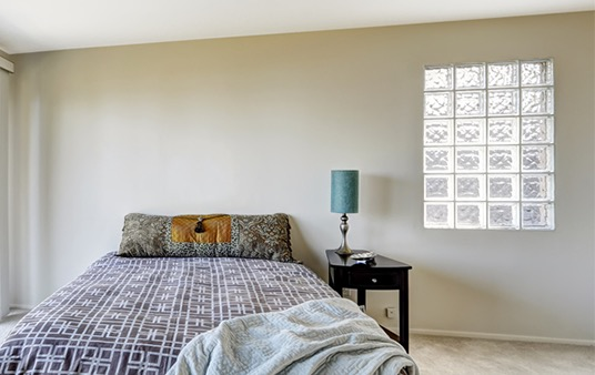 Glass block windows next to a bed in a bedroom