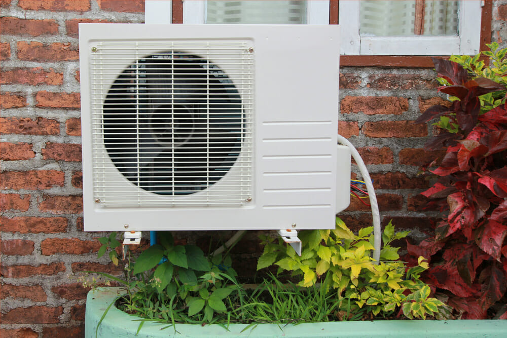 A heat pump attached to the side of a home.