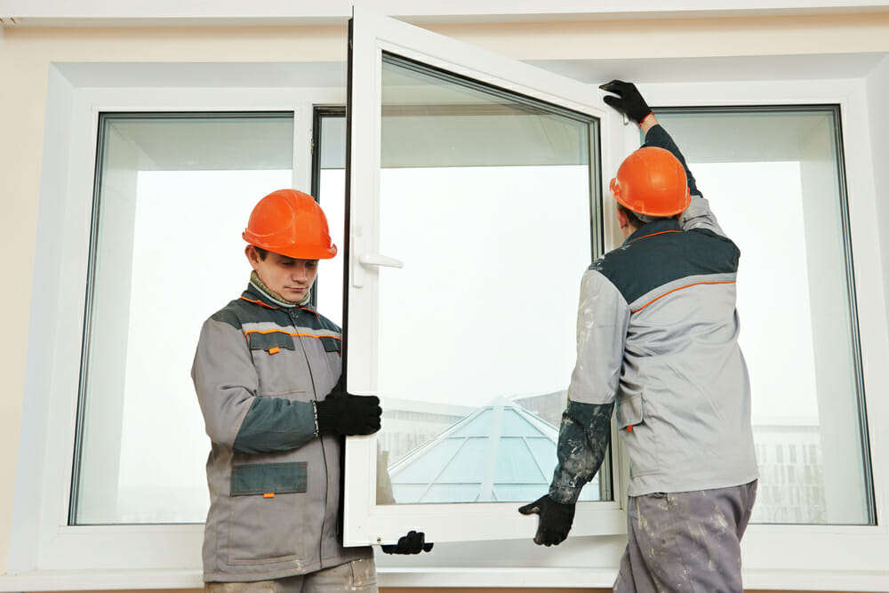 Two contractors install a window