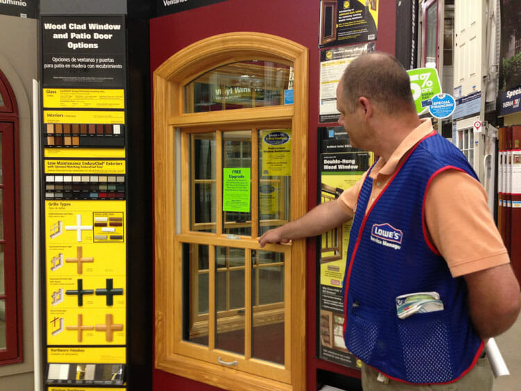 A Lowe's employee shows off a wood window