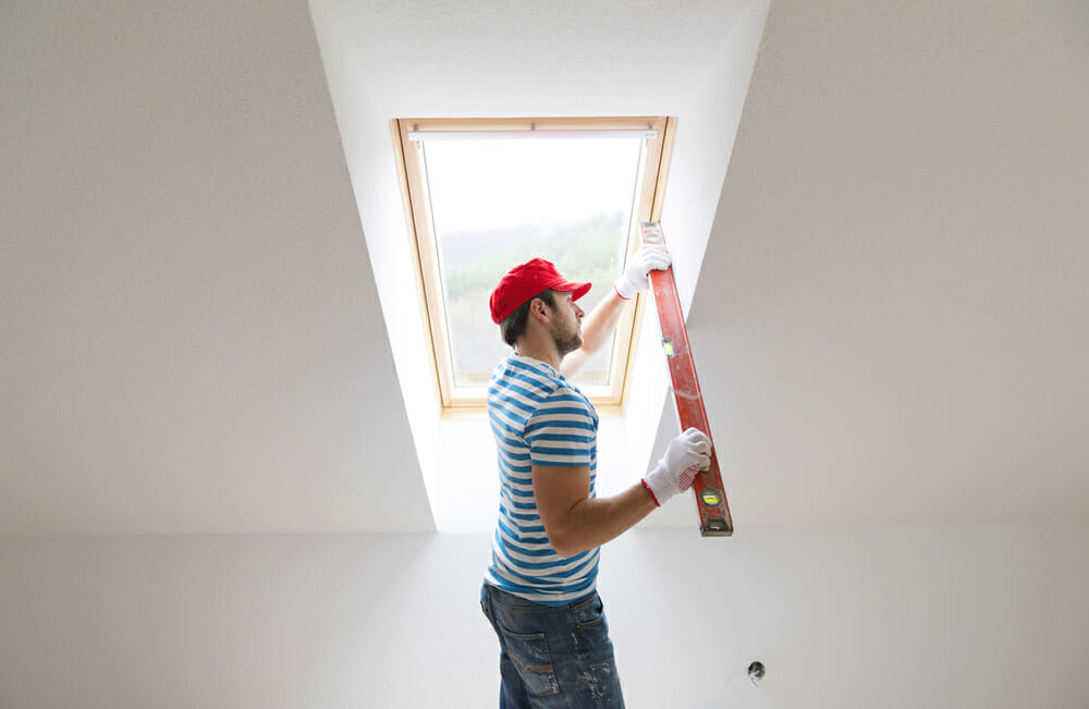 A contractor measures out the space for a skylight