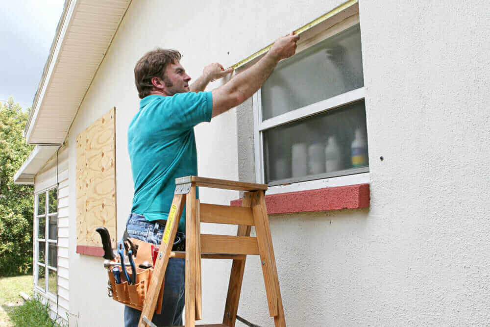 A contractor measures a window