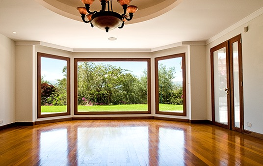 A wood floor in a living room leading to large picture windows.