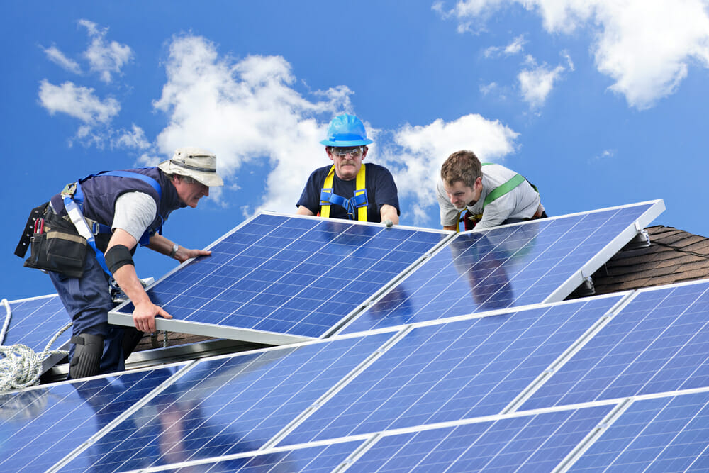 Three contractors work together to install solar panels on a home with solar rebates.
