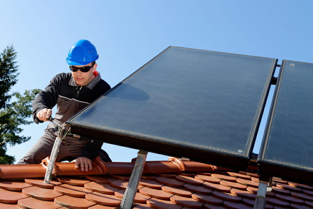 A contractor uses tools to install a solar panel on a roof.