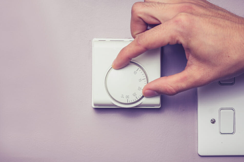 A homeowner sets the temperature on a thermostat