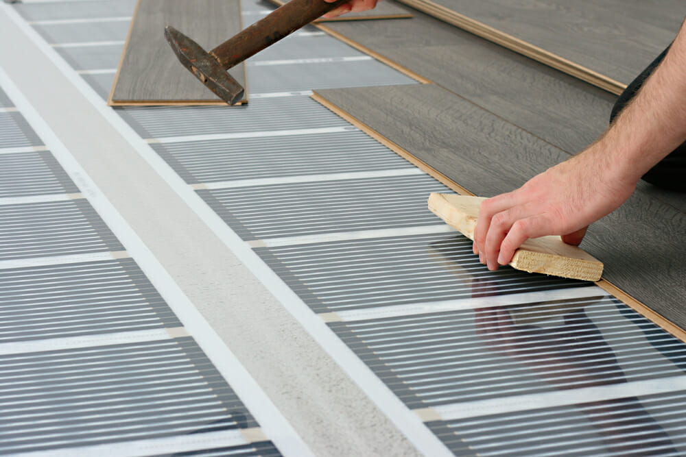 A contractor installs underfloor heating in a home.