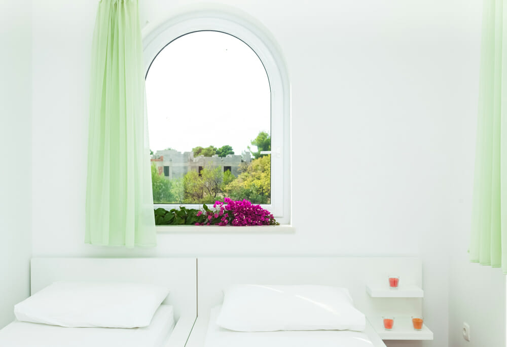 An arched window in a white home