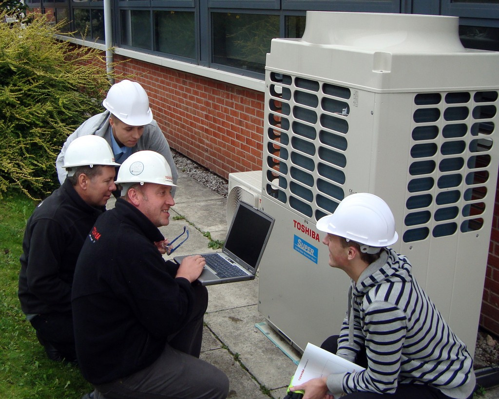 Contractors working around a Toshiba HVAC unit.