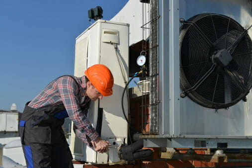 A contractor works on an aaon hvac unit.