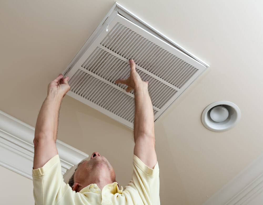 A homeowner cleans vents inside the home.