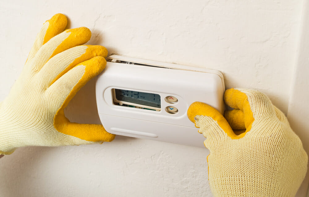 A contractor installs a thermostat in a home.