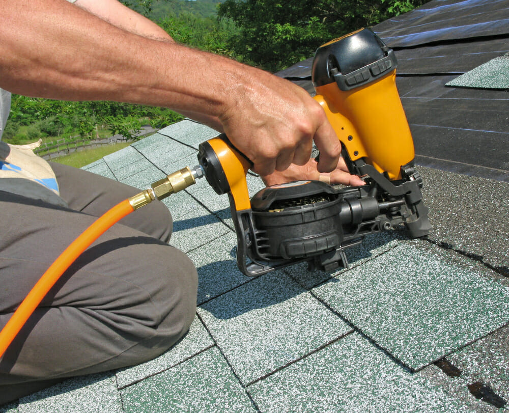 A contractor uses tools to install asphalt shingles onto a roof.