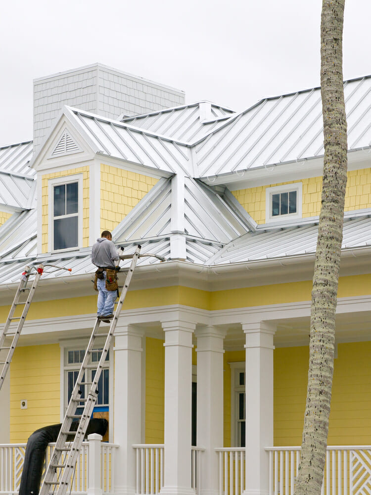 A contractor stands on a ladder and works on a roof replacement.