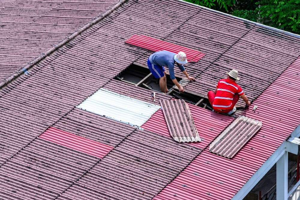Two contractors work together to replace a roof.