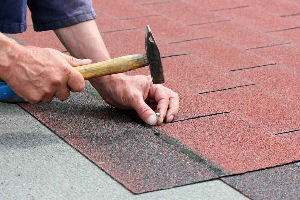 A contractor nails a shingle onto a roof.