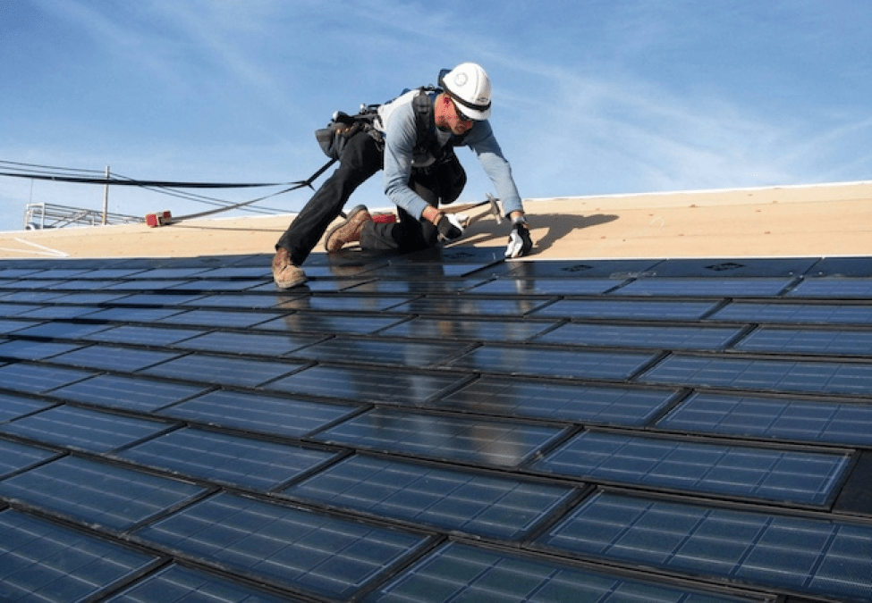 A contractor places solar shingles onto a roof.