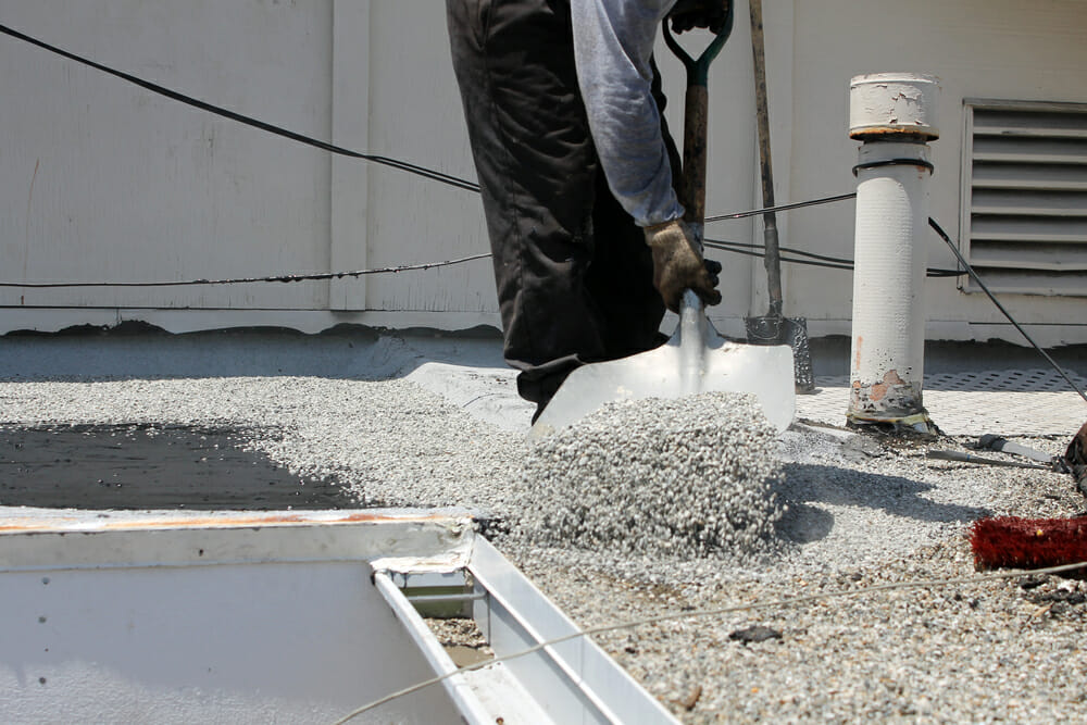A contractor uses a shovel to place gravel onto a roof.