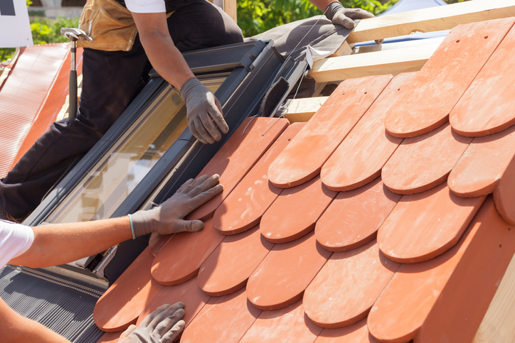 Hands of roofer laying tile on the roof. Installing natural red tile. Roof with mansard windows.