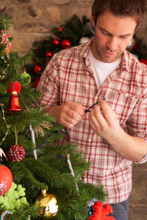 Young man fixing Christmas tree lights at home