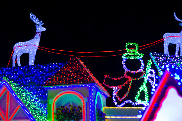 Night view of a fake house with Christmas lights, reindeer figure and snowman in the Iberoamerican Park, Santo Domingo, Dominican Republic.