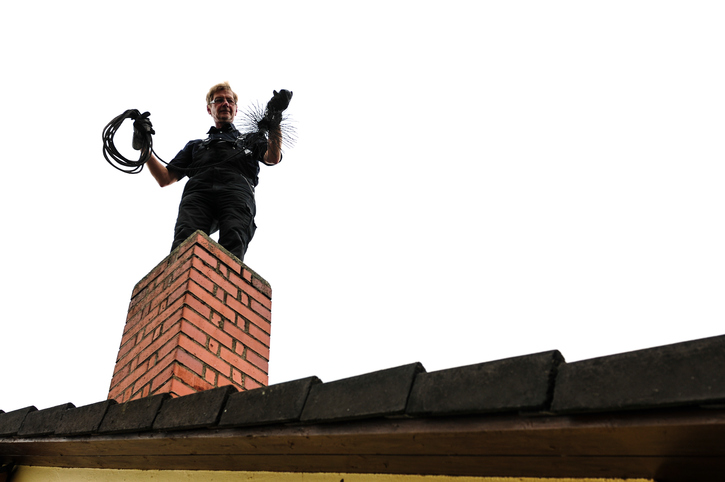 Chimney sweep is with his tool on the chimney to the fireplace to turn.