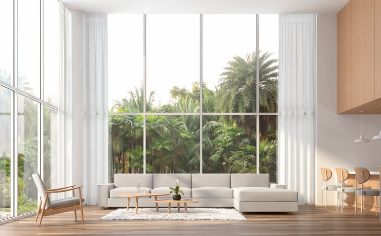 Modern contemporary high ceiling living room 3d render.The Rooms have wooden floors,white and wood wall.furnished with white fabric furniture.There are large window. Overlooks to palm garden.