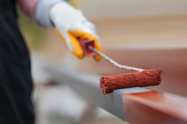 Worker painting square steel tube with paintroller selective focus