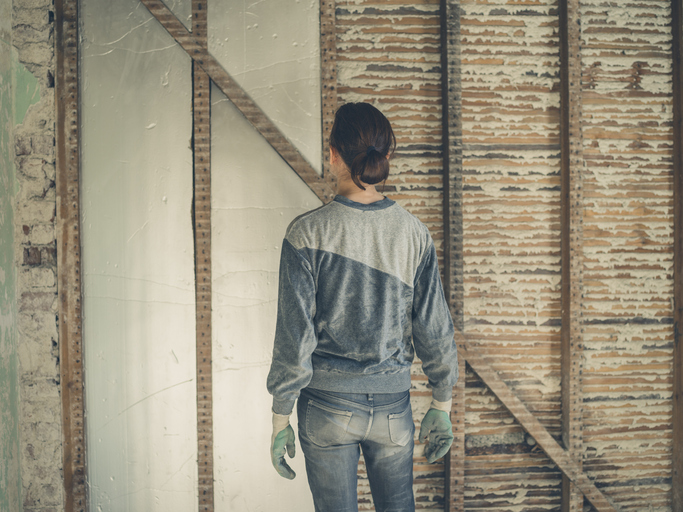 A Young Woman Is Standing In Loft Room And Looking At The Insulation She