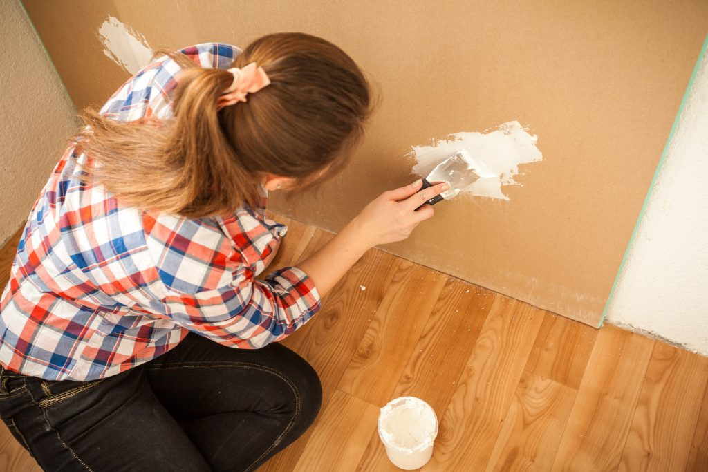 Brunette woman plastering wall at house