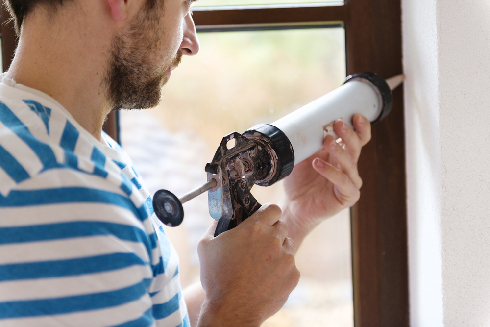man using caulking gun