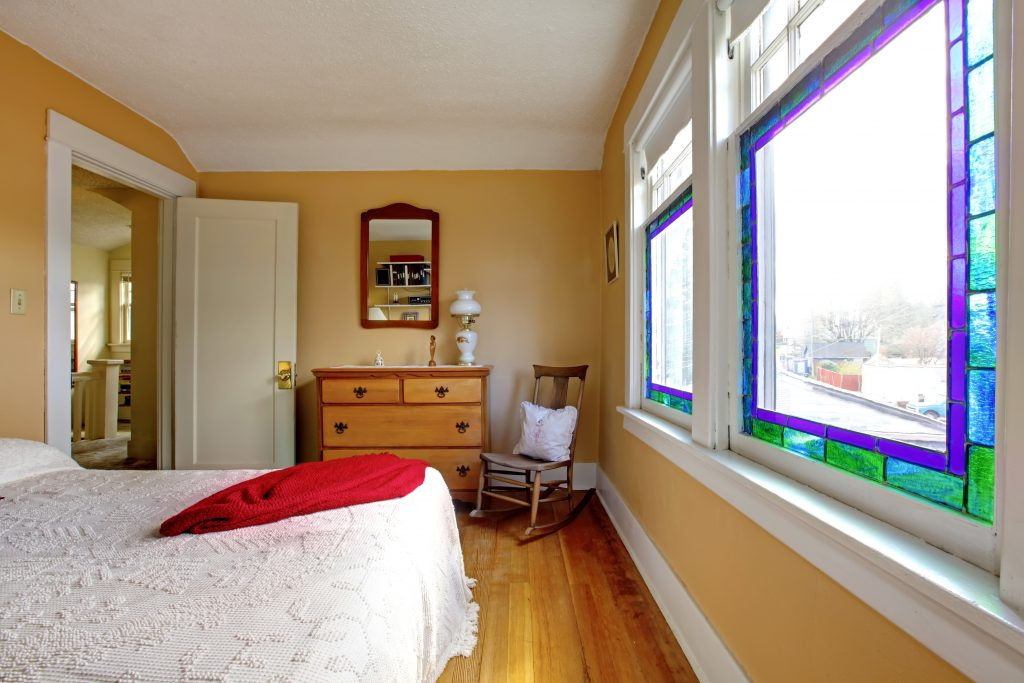 English old bedroom with yellow walls and white bed.