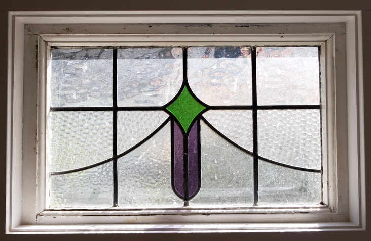 A Small Stained Glass Window With Green And Purple Sections