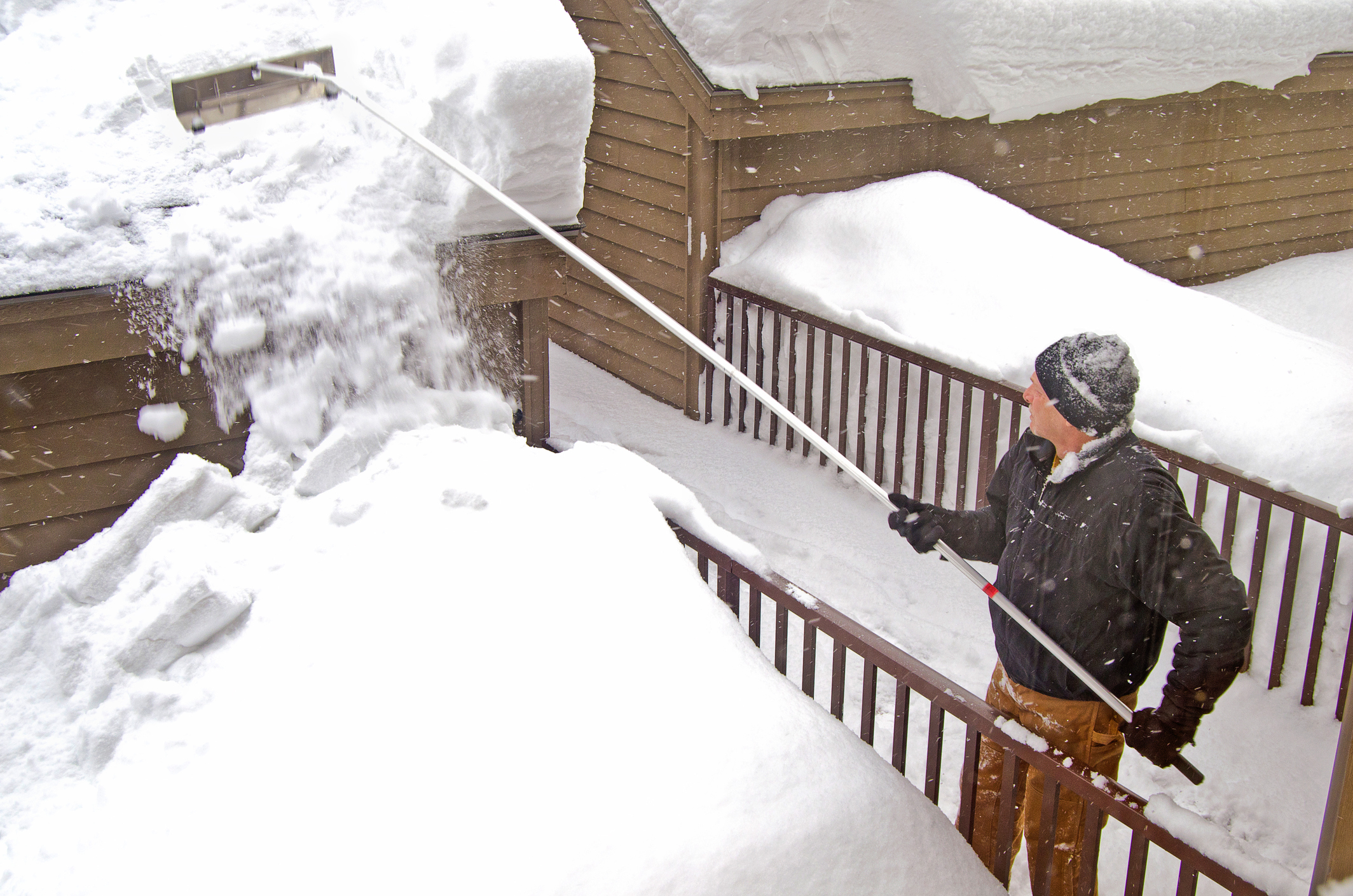 man using snow rake